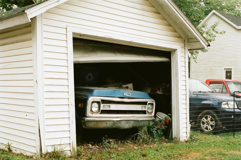 broken garage door with blue truck inside