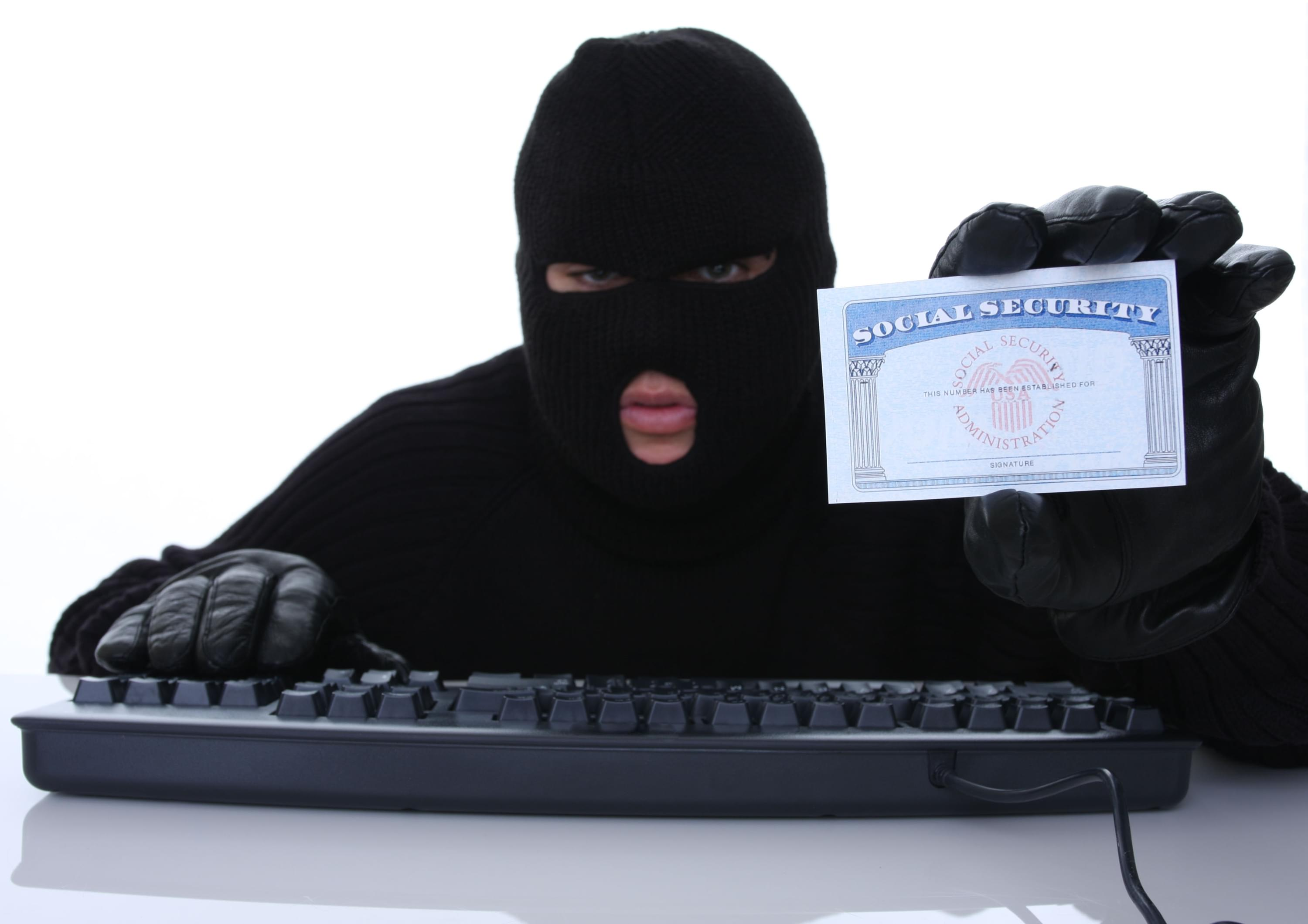 Person in ski mask at a computer keyboard holding a social security card