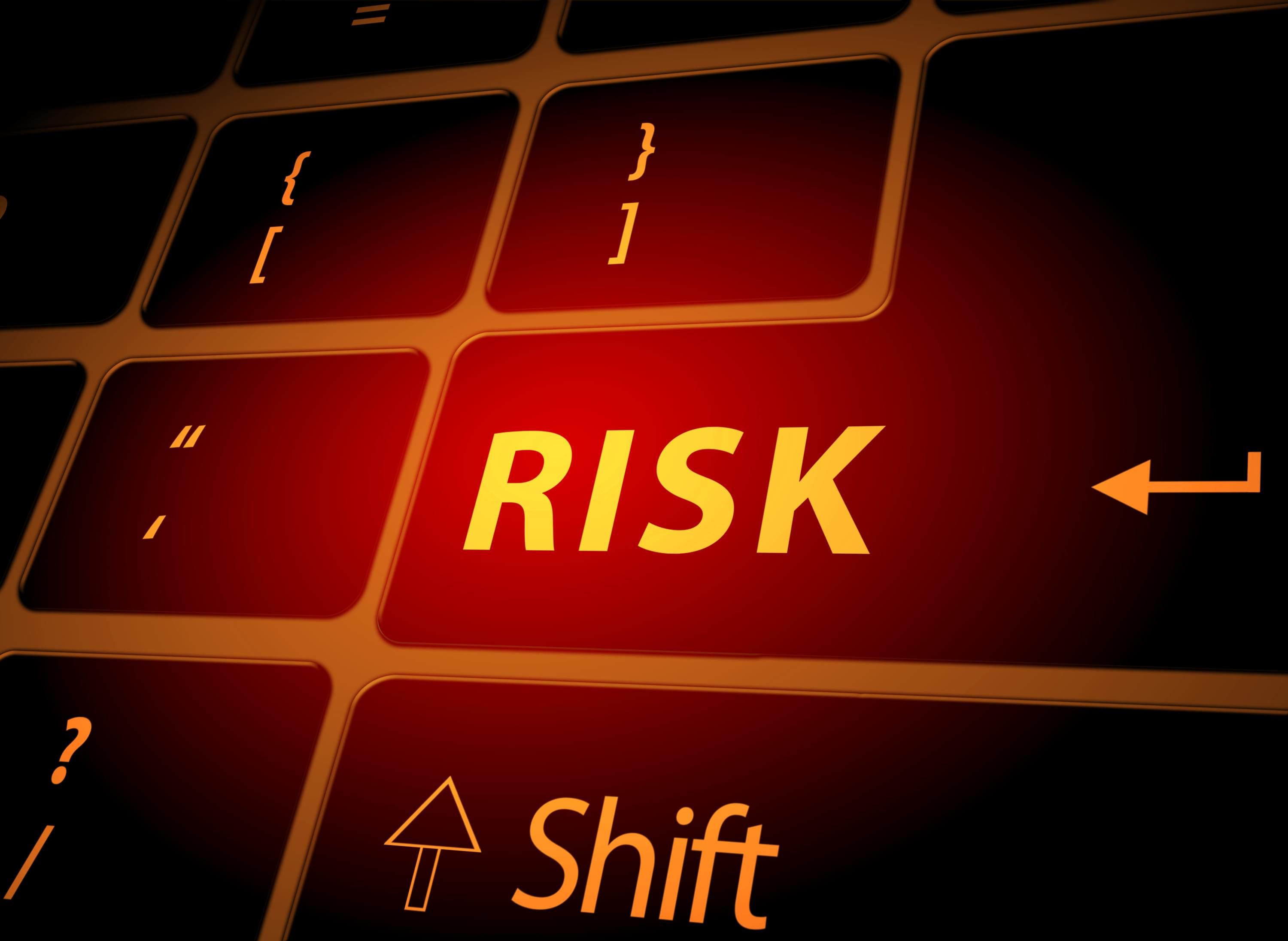 "Computer keyboard with the word ""risk"" in bright orange"
