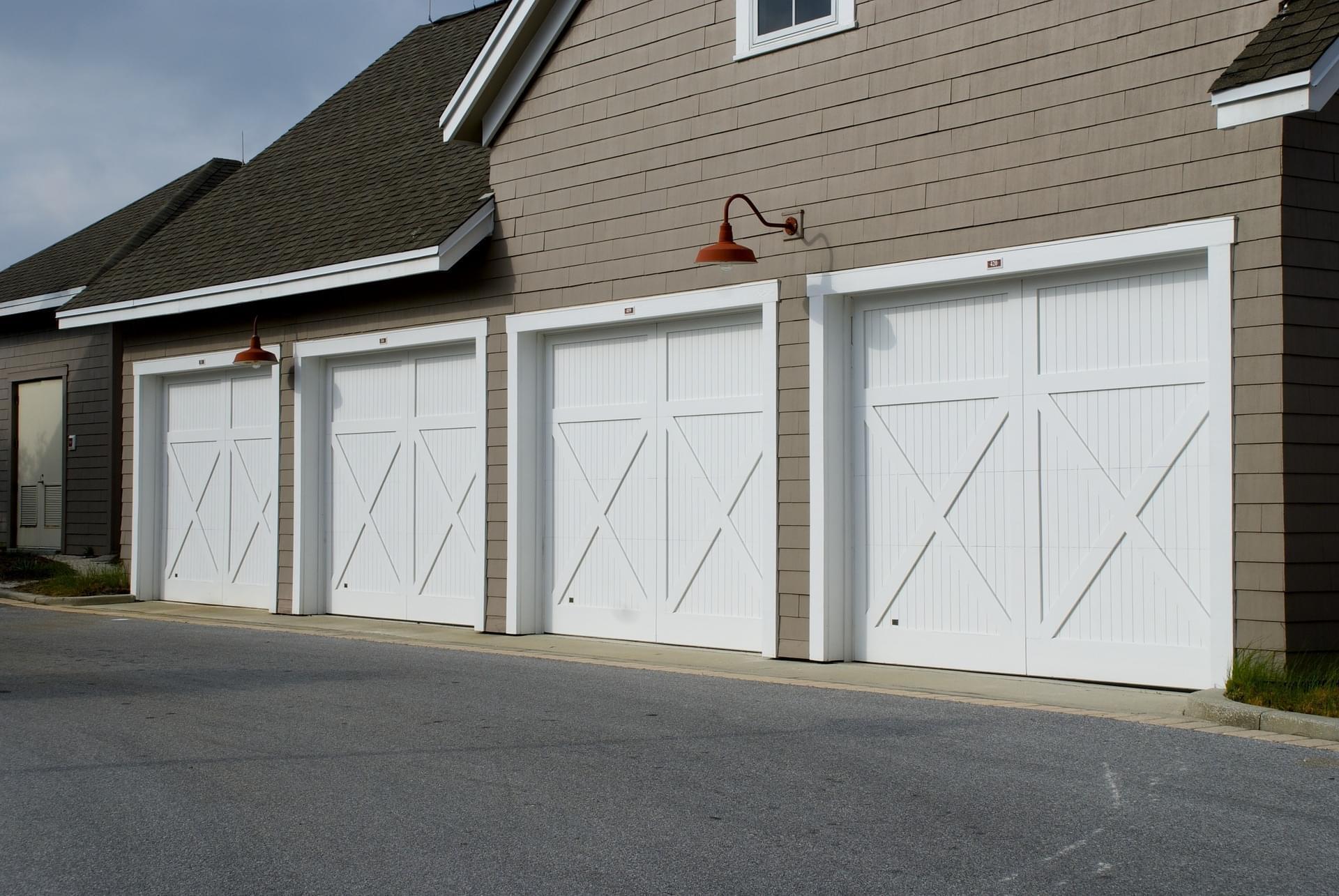 row of four white sliding garage doors