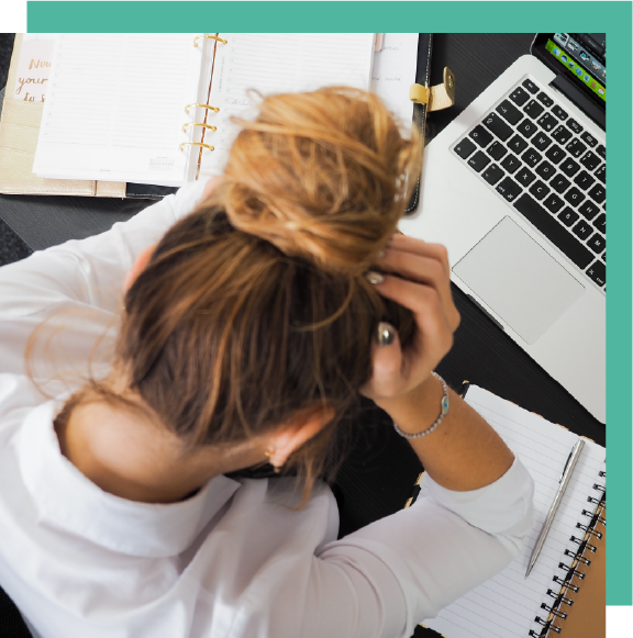 Aerial view of a stressed woman sitting at her desk with her head in her palms