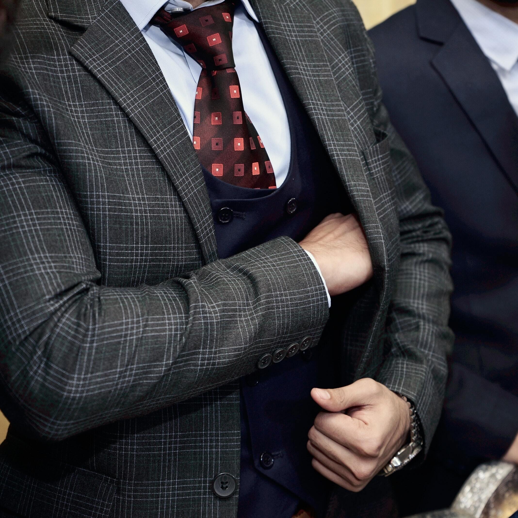 Auf diesem Bild ist ein Mann im Anzug zusehen und nach seiner Geldbörse in seinem Sakko greift.