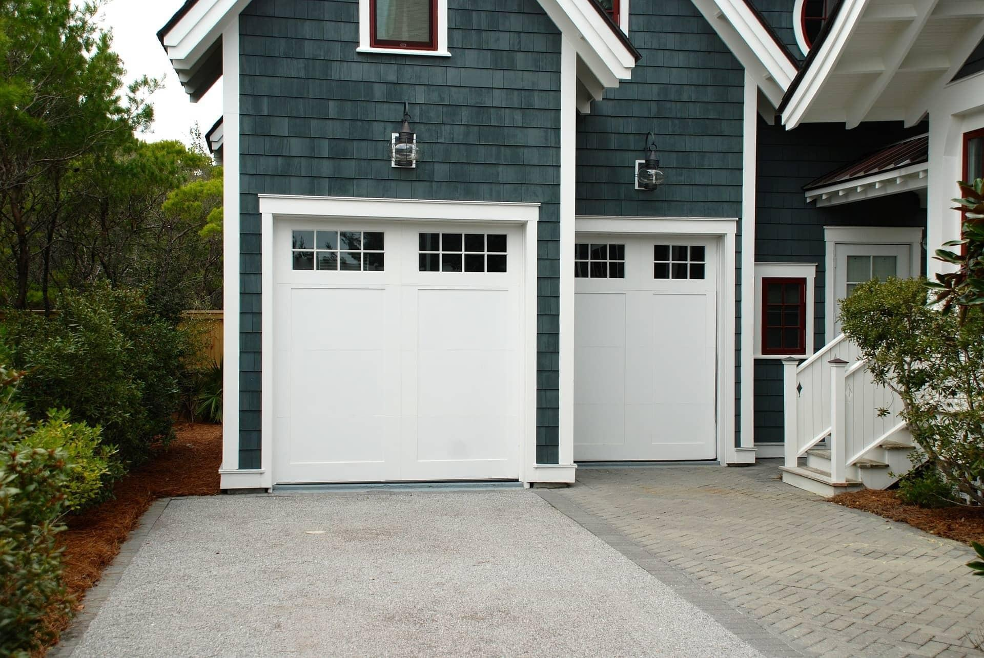 two white garage doors in blue house