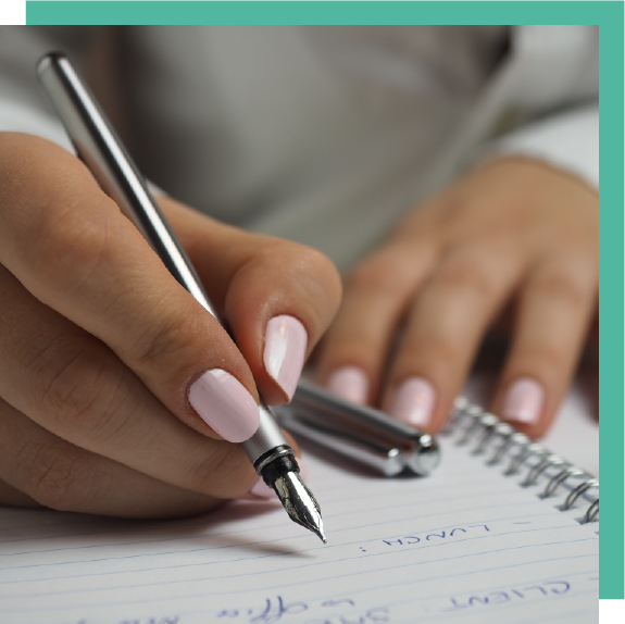 Woman's hands with light pink nails writing in a journal
