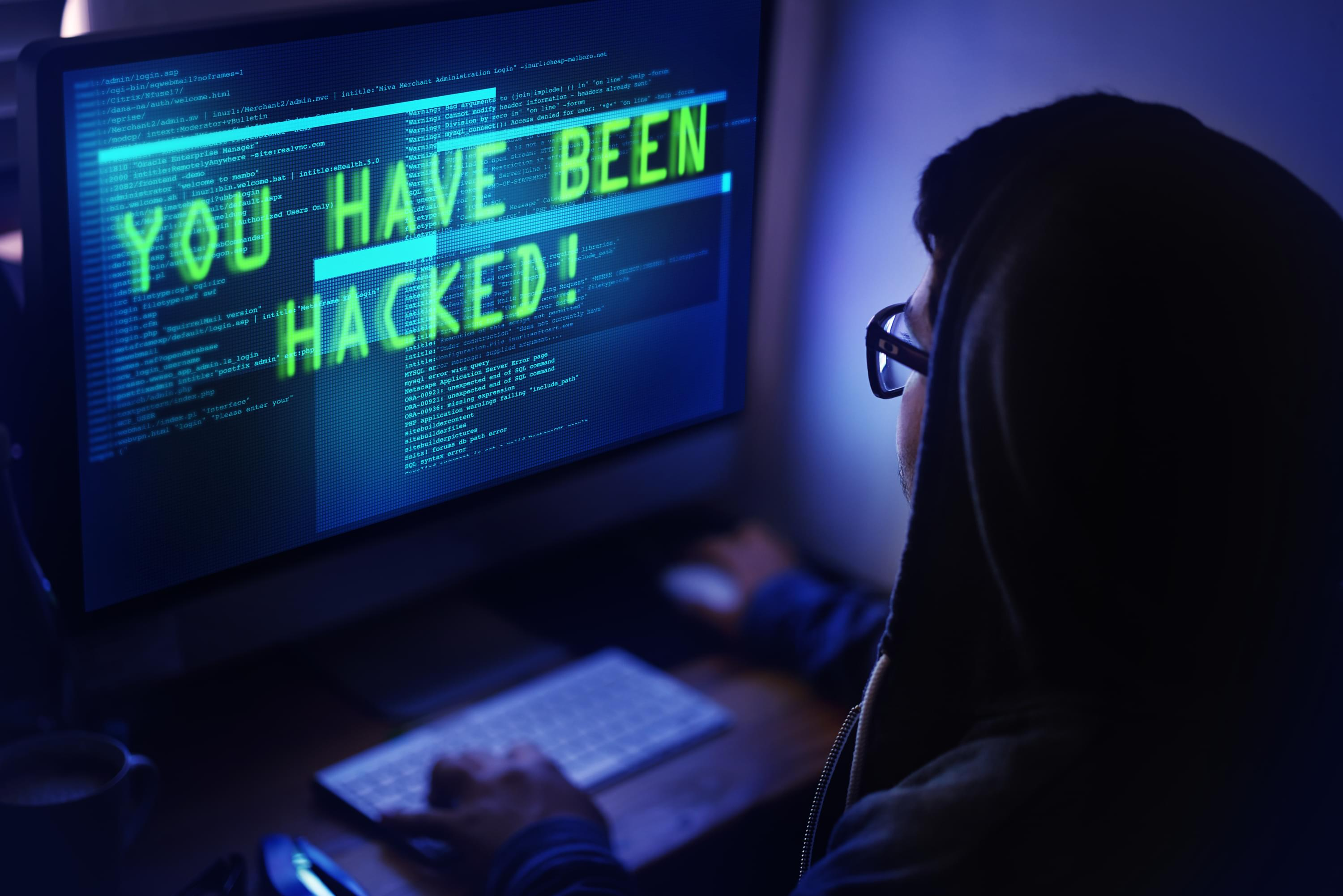 "Person looking at computer screen with words ""you have been hacked!"""