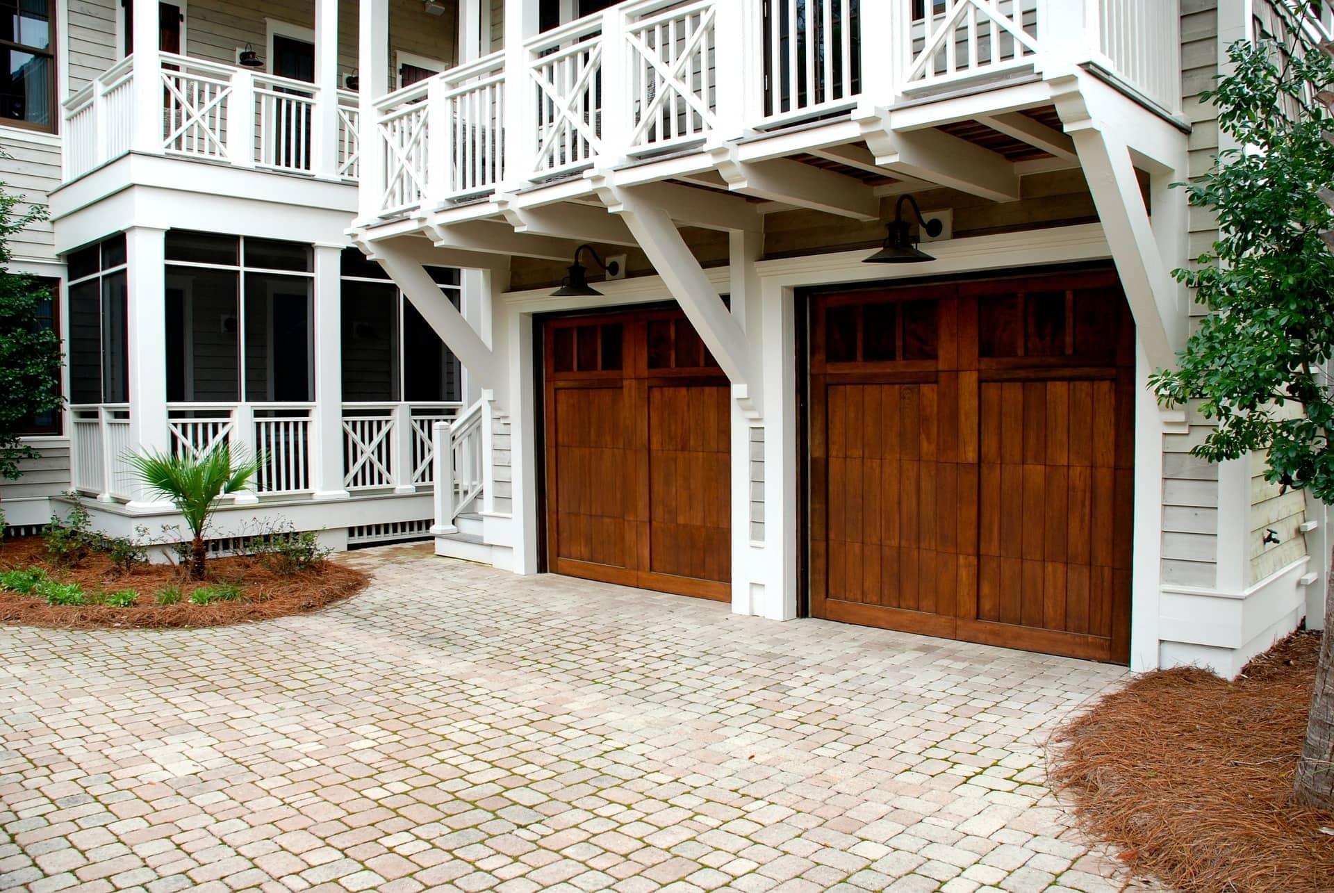 two wood paneled garage doors under balcony
